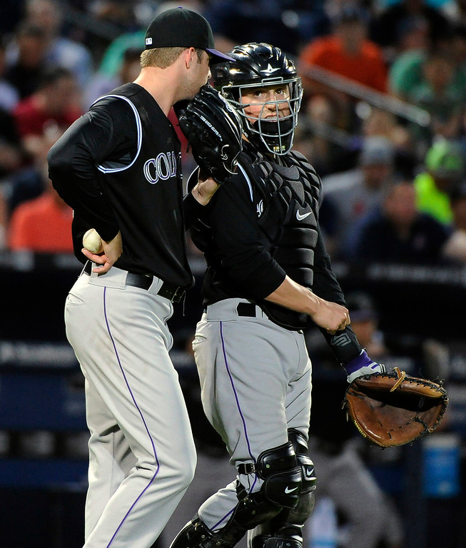 . Colorado Rockies starting pitcher Jordan Lyles, left, and catcher Jordan Pacheco talk near the mound with two Atlanta Braves runners in scoring position during the third inning of a baseball game Friday, May 23, 2014, in Atlanta. (AP Photo/David Tulis)