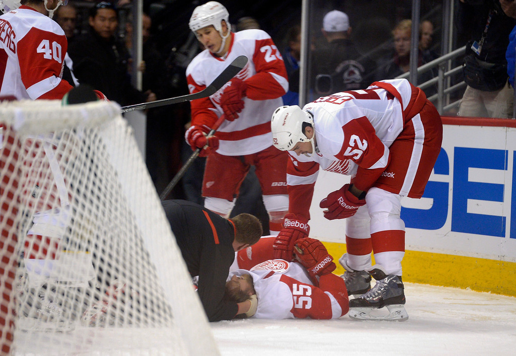 . Detroit Red Wings defenseman Niklas Kronwall (55) is looked at by trainers after a hit up against the boards during the first period by Colorado Avalanche left wing Cody McLeod (55) October 17, 2013 at Pepsi Center. Niklas Kronwall was taken off the ice by stretcher. (Photo by John Leyba/The Denver Post)