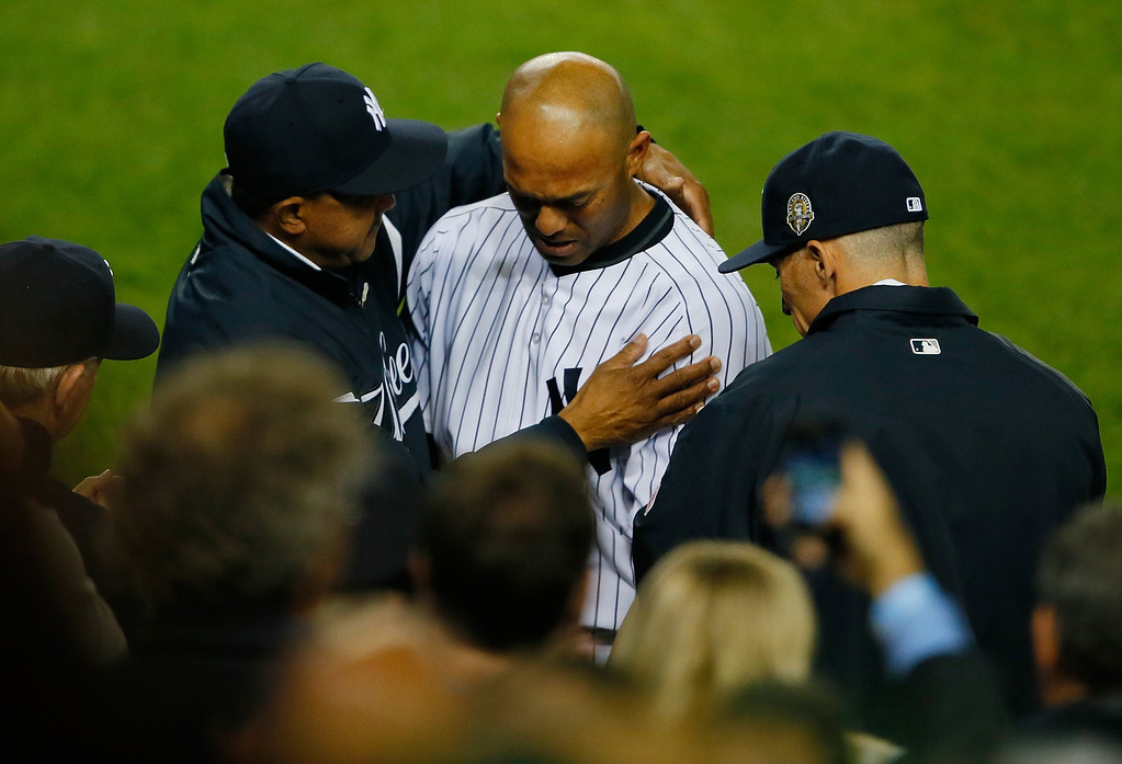 . Mariano Rivera #42 of the New York Yankees hugs Manager Joe Girardi #28 and Tony Pena #56 after leaving the game against the Tampa Bay Rays in the ninth inning at Yankee Stadium on September 26, 2013 in the Bronx borough of New York City.  (Photo by Mike Stobe/Getty Images)