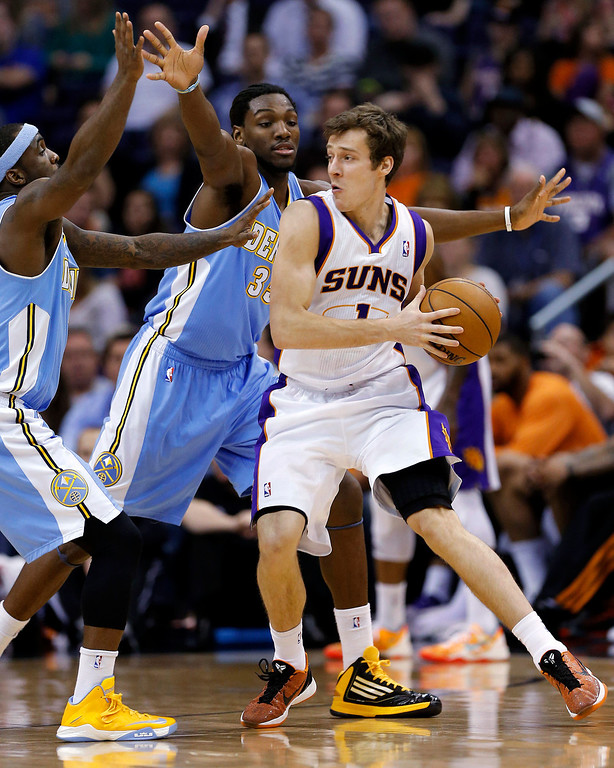 . Phoenix Suns\' Goran Dragic (1), of Slovenia, looks to pass around Denver Nuggets\' Kenneth Faried (35) and Corey Brewer during the first half of an NBA basketball game, Monday, March 11, 2013, in Phoenix. (AP Photo/Matt York)