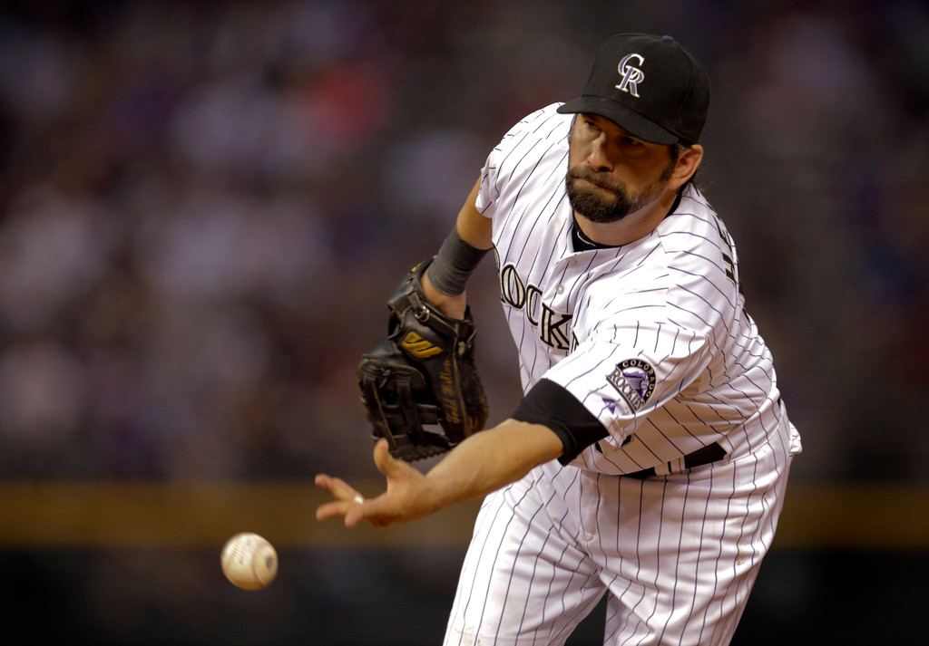. Colorado Rockies first baseman Todd Helton tosses the ball to pitcher Jorge De La Rosa to out  Washington Nationals baserunner Denard Span in the sixth inning of a baseball game on Wednesday, June 12, 2013 in Denver. (AP Photo/Joe Mahoney)