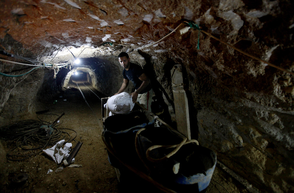 . In this Monday, Sept. 30, 2013 photo, a Palestinian man works in a smuggling tunnel in Rafah, on the border between Egypt and the southern Gaza Strip. Since the summer, Egyptís military has tried to destroy or seal off most of the smuggling tunnels under the Gaza-Egypt border, a consequence of the heightened tensions between Cairo and the Hamas government in Gaza. The tunnels once employed thousands of young men in Gaza. By early September, with most tunnels closed, only few tunnel workers reported to their jobs for maintenance work. Some mask their faces with shirts to avoid identification while working, for fear of repercussions in case they were to travel to Egypt in the future. (AP Photo/Hatem Moussa)