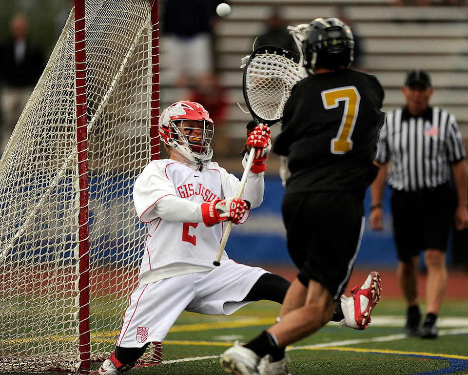 . Arapahoe High School senior attacker Tyler Widlund #7 scores a goal against Regis Jesuit sophomore goalie Bret Quartuccio #2  during a CHSAA 5A boys lacrosse semifinal game at All City Stadium on May 15, 2013, in Denver, Colorado. Arapahoe won 13-5 to advance to the finals. (Photo by Daniel Petty/The Denver Post)