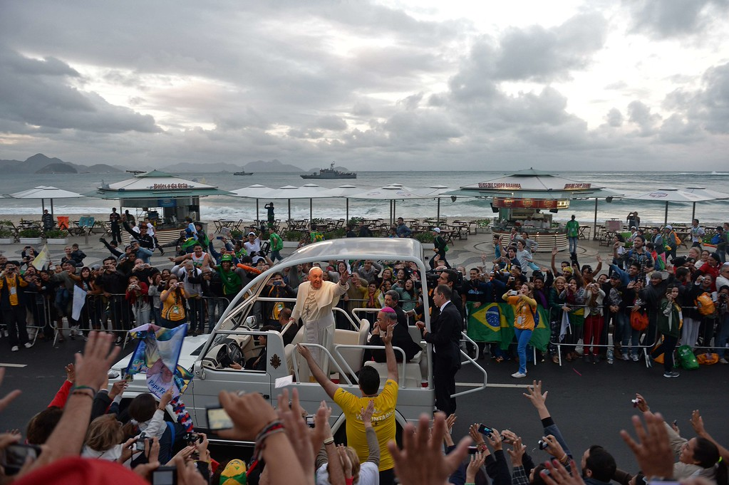 ". Pope Francis waves at faithfuls standing on the beachfront as he arrives on the popemobile at Copacabana beach to participate in a re-enactment of the 14 Stations of the Cross -- scenes of Jesus carrying the cross to his crucifixion -- in Rio de Janeiro, on July 26, 2013. Pope Francis, who is in Rio for the weeklong gathering of young Catholics World Youth Day, took his high-octane mission to ""shake up\"" Catholic faith back to the streets of Brazil Friday, greeting throngs of pilgrims, meeting convicts and hearing youngsters confess their sins.  EVARISTO SA/AFP/Getty Images"
