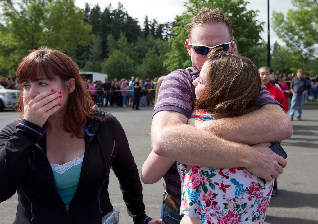 . A Reynolds High School student is reunited with her parents after a shooting at her school June 10, 2014 in Troutdale, Oregon. (Photo by Natalie Behring/Getty Images)