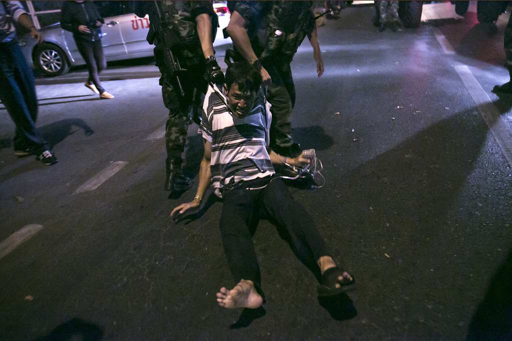 . A Thai protester is dragged away by the Thai military during an anti-coup protest May 23, 2014 in Bangkok, Thailand. The Army chief announced yesterday that the armed forces were seizing power in a non-violent coup. Thailand has seen many months of political unrest and violence which has claimed at least 28 lives. Thailand is known as a country with a very unstable political record, it is now experiencing it\'s 12th coup with 7 attempted pervious coups. (Photo by Paula Bronstein/Getty Images)