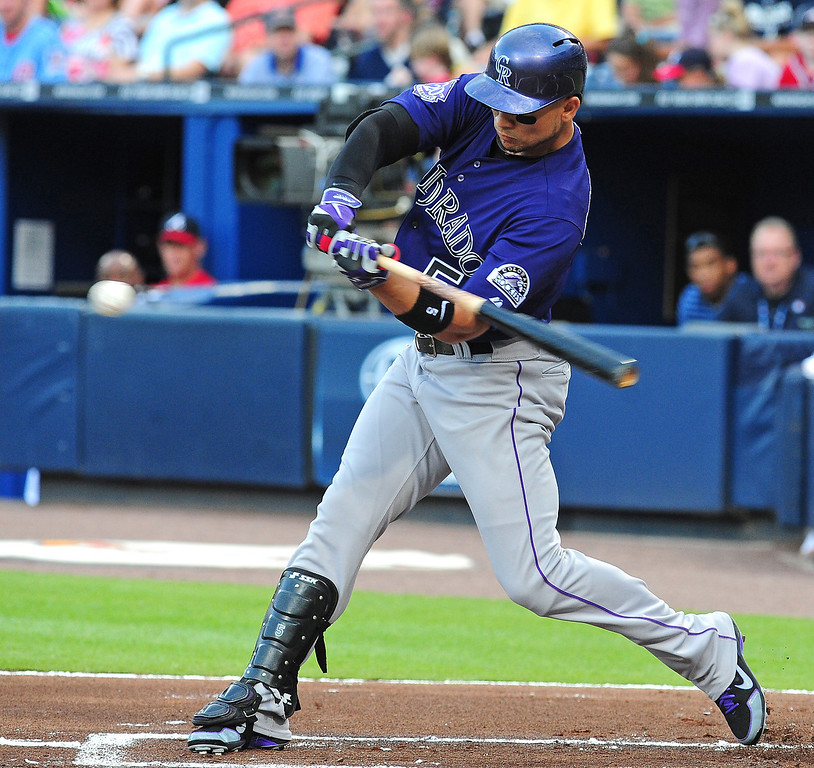 . Carlos Gonzalez #5 of the Colorado Rockies hits a run scoring single against the Atlanta Braves at Turner Field on July 29, 2013 in Atlanta, Georgia. (Photo by Scott Cunningham/Getty Images)