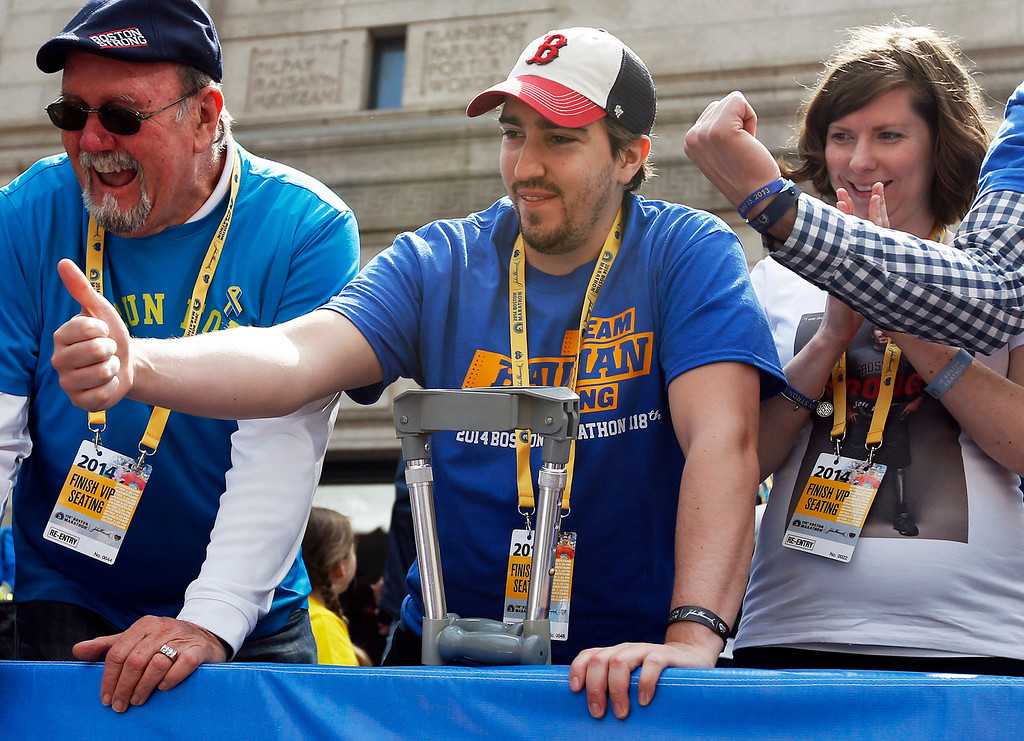 . Bombing survivor Jeff Bauman, center, cheers for Meb Keflezighi who won the 118th Boston Marathon, Monday, April 21, 2014, in Boston. Bauman suffered traumatic injuries in the bombings near the finish line last year. At right is his fiancee Erin Hurley. (AP Photo/Elise Amendola)
