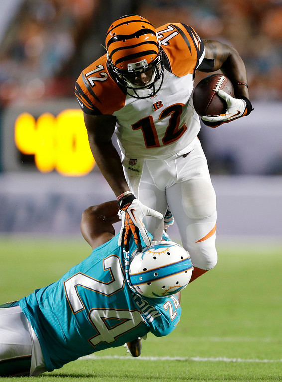 . Miami Dolphins cornerback Dimitri Patterson (24) tackles Cincinnati Bengals wide receiver Mohamed Sanu (12) during the first half of an NFL football game, Thursday, Oct. 31, 2013, in Miami Gardens, Fla. (AP Photo/Wilfredo Lee)