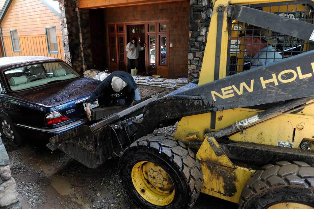 . BOULDER, CO - SEPTEMBER 13: Boulder Colorado resident, Geoffrey Pollich, center, places a railroad tie between his car\'s bumper and the shovel of front a skid loader driven by friend, Matt Corley, to try and push Pollich\'s car, stuck in the mud and rocks in front of his house  along Juniper Ave. Friday afternoon, September 13, 2013. (Photo By Andy Cross/The Denver Post)