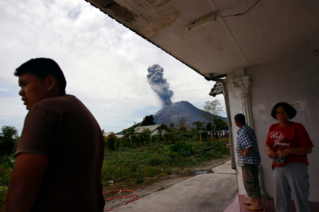 . Residents watch from their house as Mount Sinabung erupts in Karo, North Sumatra, Indonesia, Tuesday, Sept. 17, 2013. Thousands of people were evacuated from their villages following the eruption of the 2,600-meter (8,530-feet) volcano Sunday after being dormant for three years, sending thick ash into the sky with small rocks pelting neighboring villages.   (AP Photo/Binsar Bakkara)