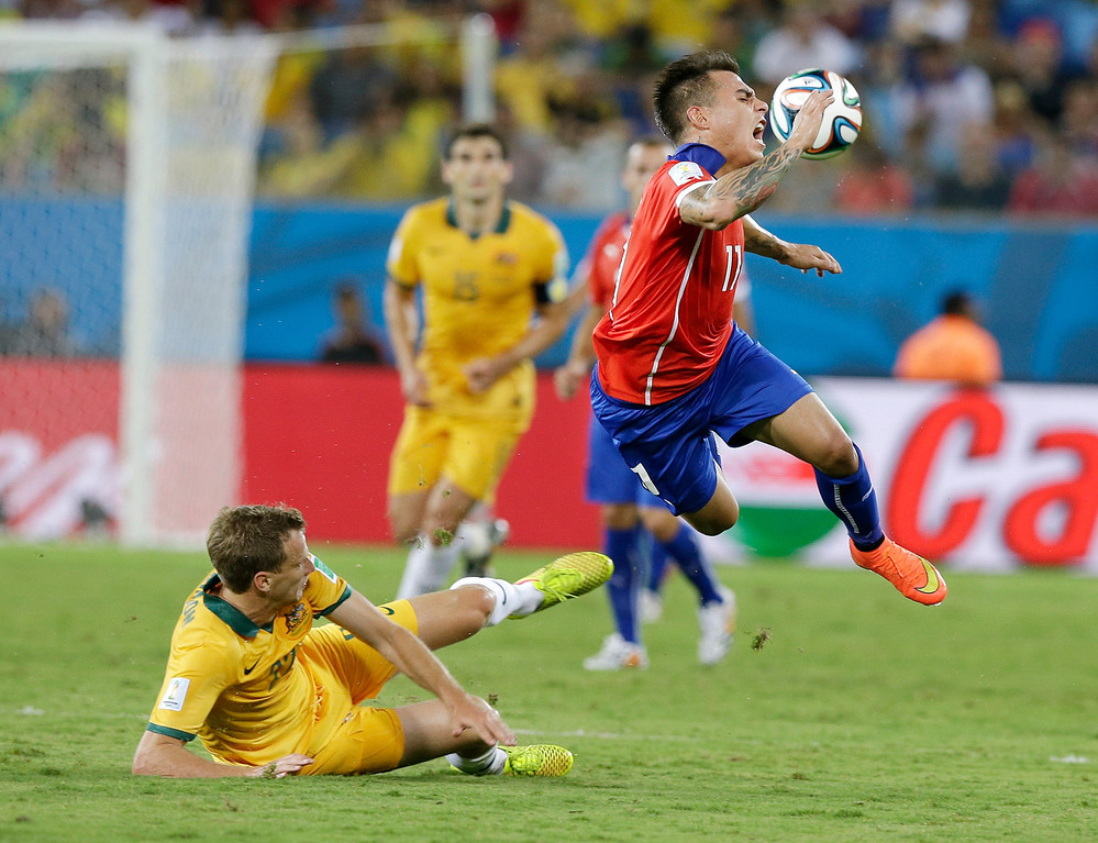 . Australia\'s Alex Wilkinson, left, trips up Chile\'s Eduardo Vargas (11) during the first half of the group B World Cup soccer match between Chile and Australia in the Arena Pantanal in Cuiaba, Brazil, Friday, June 13, 2014. (AP Photo/Thanassis Stavrakis)