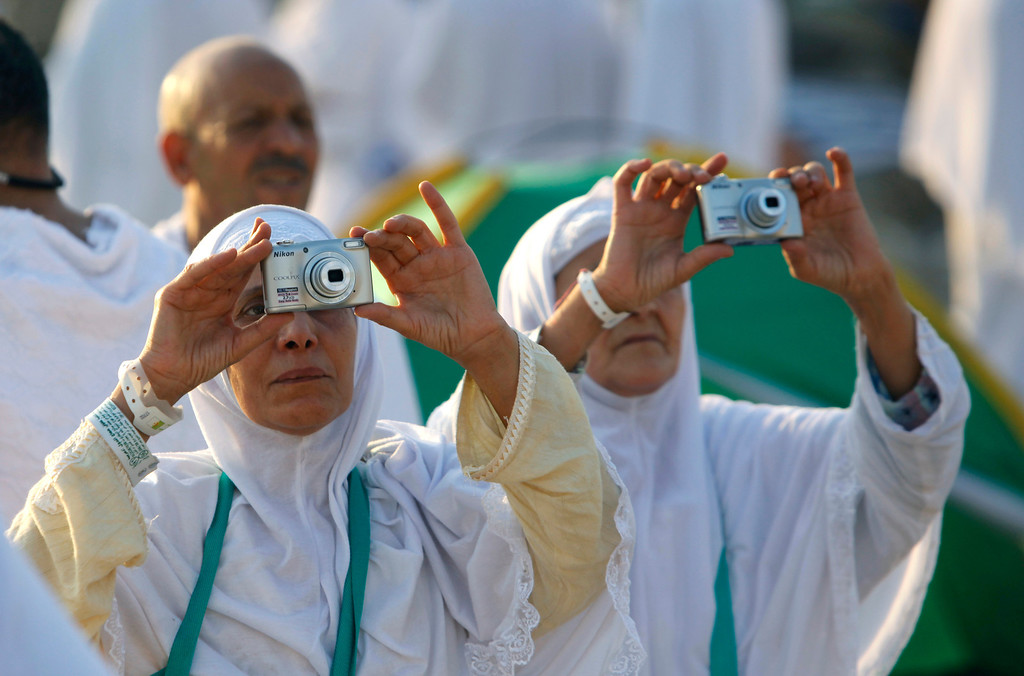 . Algerian Muslim pilgrims take pictures on a rocky hill called the Mountain of Mercy, on the Plain of Arafat near the holy city of Mecca, Saudi Arabia, Monday, Oct. 14, 2013.  (AP Photo/Amr Nabil)