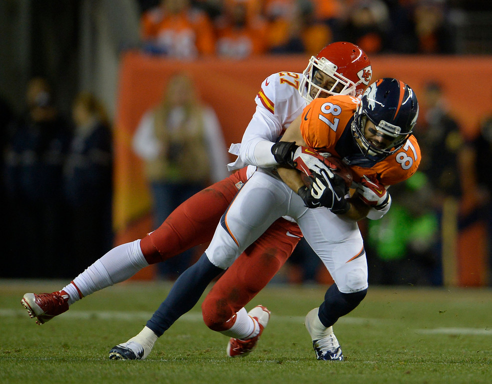 . Denver Broncos wide receiver Eric Decker (87) is tackled by Kansas City Chiefs cornerback Sean Smith (27) in the second quarter. The Denver Broncos take on the Kansas City Chiefs at Sports Authority Field at Mile High in Denver on November 17, 2013. (Photo by Joe Amon/The Denver Post)