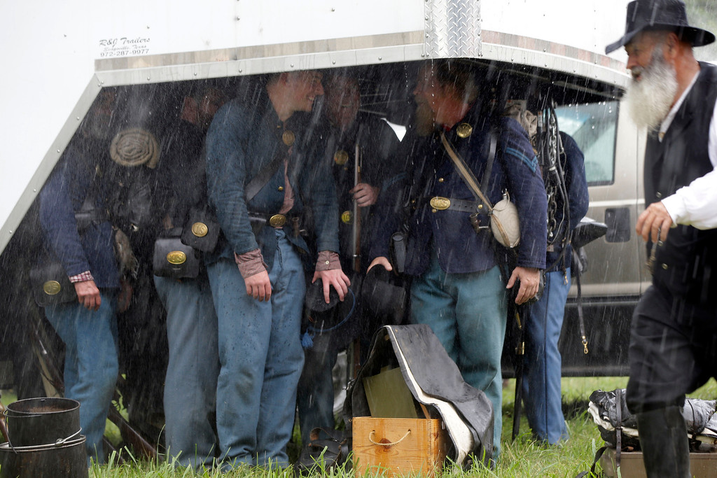 . Union reenactors seek shelter from a driving rainstorm under a trailer during ongoing activities commemorating the 150th anniversary of the Battle of Gettysburg, Thursday, June 27, 2013, in Gettysburg, Pa.  (AP Photo/Matt Rourke)