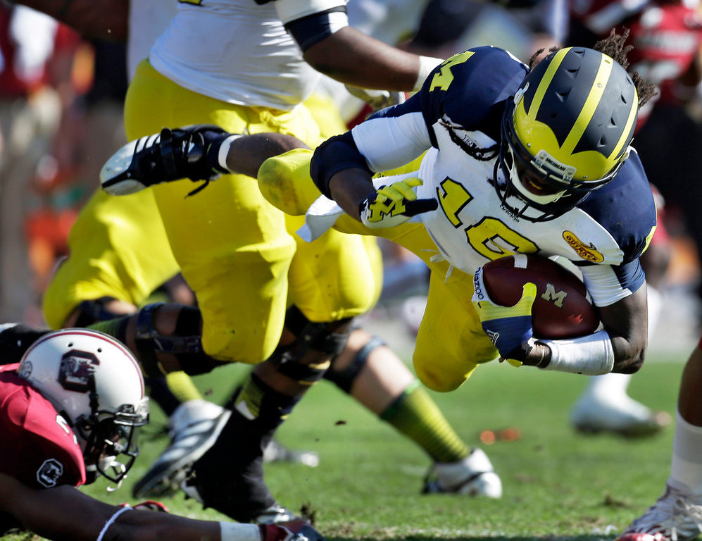 . Michigan quarterback Denard Robinson (16) is tripped up by South Carolina linebacker DeVonte Holloman (21) during the first quarter of the Outback Bowl NCAA college football game, Tuesday, Jan. 1, 2013, in Tampa, Fla. (AP Photo/Chris O\'Meara)