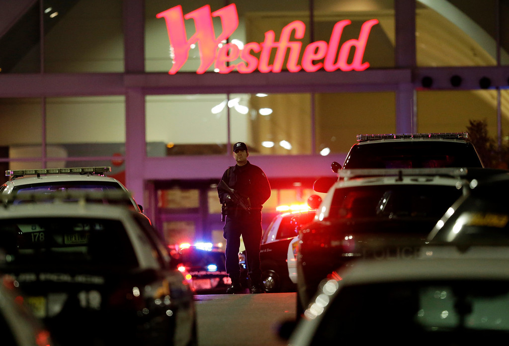 . An official walks with a semi-automatic weapon on the parking lot of Garden State Plaza Mall following reports of a shooter, Tuesday, Nov. 5, 2013, in Paramus, N.J. Hundreds of law enforcement officers converged on the mall Monday night after witnesses said multiple shots were fired there. (AP Photo/Julio Cortez)
