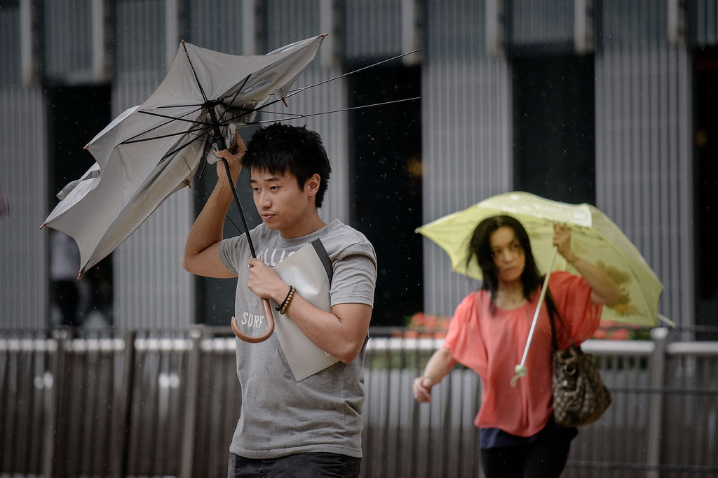. A man holds his broken umbrella against heavy winds in Hong Kong on August 13, 2013 as the city braces for deadly Typhoon Utor which earlier swept through the Philippines. The strongest typhoon to hit the Philippines this year caused floods and landslides, killing at least two people as rescuers raced to reach isolated villages in the storm\'s path.   PHILIPPE LOPEZ/AFP/Getty Images