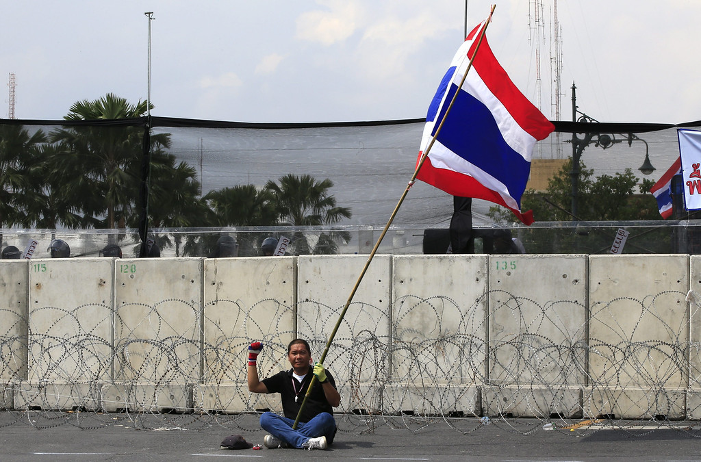. A Thai anti-government protester sits alone with his fist raised and holding a Thai flag in front of a cement and wire barricade facing the Government House, as a no-confidence motion is put before a barricaded parliament, only a block away, by the opposition Democrat Party on the performance of the Thai Prime Minister Yingluck Shinawatra, in Bangkok, Thailand, 26 November 2013.  EPA/BARBARA WALTON