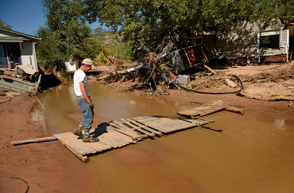 . Bob Smith makes his way back to his destroyed home in Lyons to looks for more belongings he can save, September 20, 2013. Residents in Lyon got to go back to the area after the massive flood destroyed much of the mountain town. (Photo By RJ Sangosti/The Denver Post)