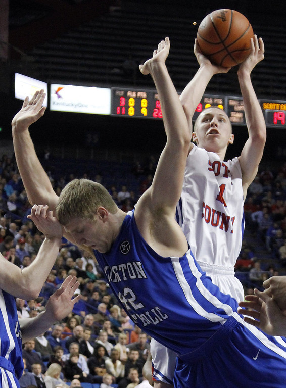 . Scott County\'s Hines Jones, right, shoots as Covington Catholic\'s Mark Schult defends during the championship game of the KHSAA Sweet 16 high school basketball tournament in Lexington, Ky., Sunday, March 23, 2014. Covington Catholic won in overtime 59-51. (AP Photo/James Crisp)