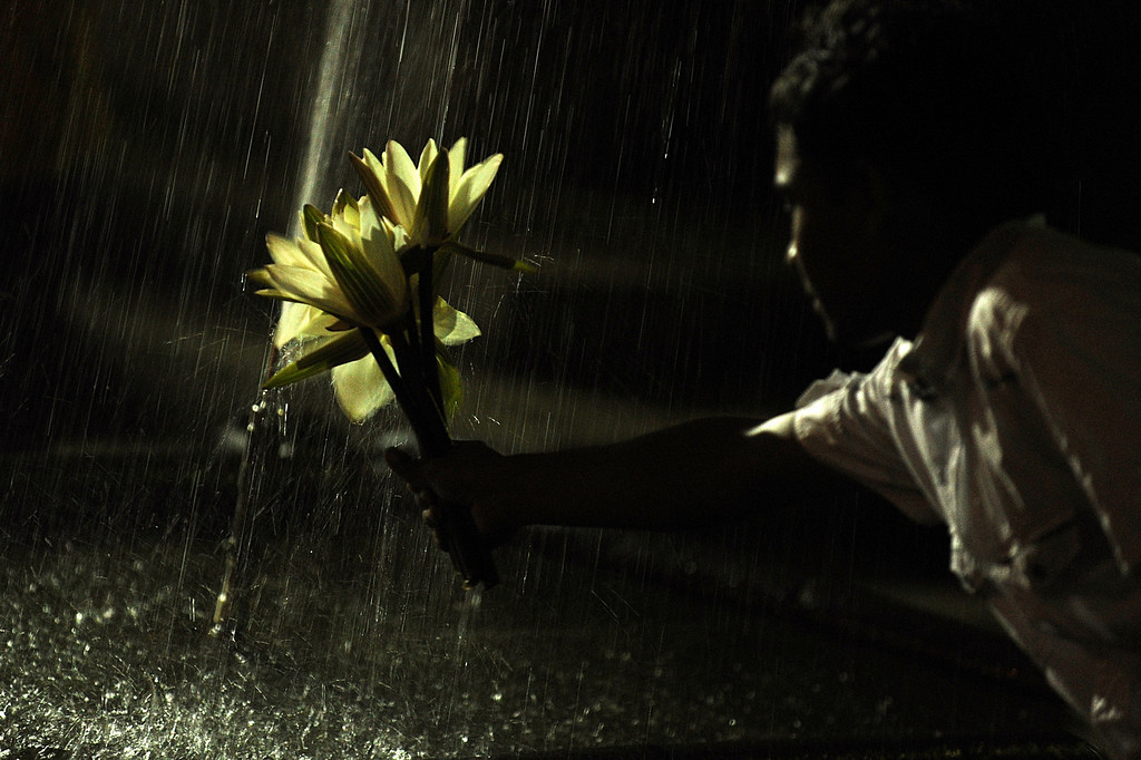 . A Sri Lankan Buddhist holds out flowers under a fountain before praying at the Kelaniya Temple on December 31, 2012, in Kelaniya. Many Sri Lankans marked the beginning of the 2013 New Year with religious ceremonies.   Ishara S.KODIKARA/AFP/Getty Images
