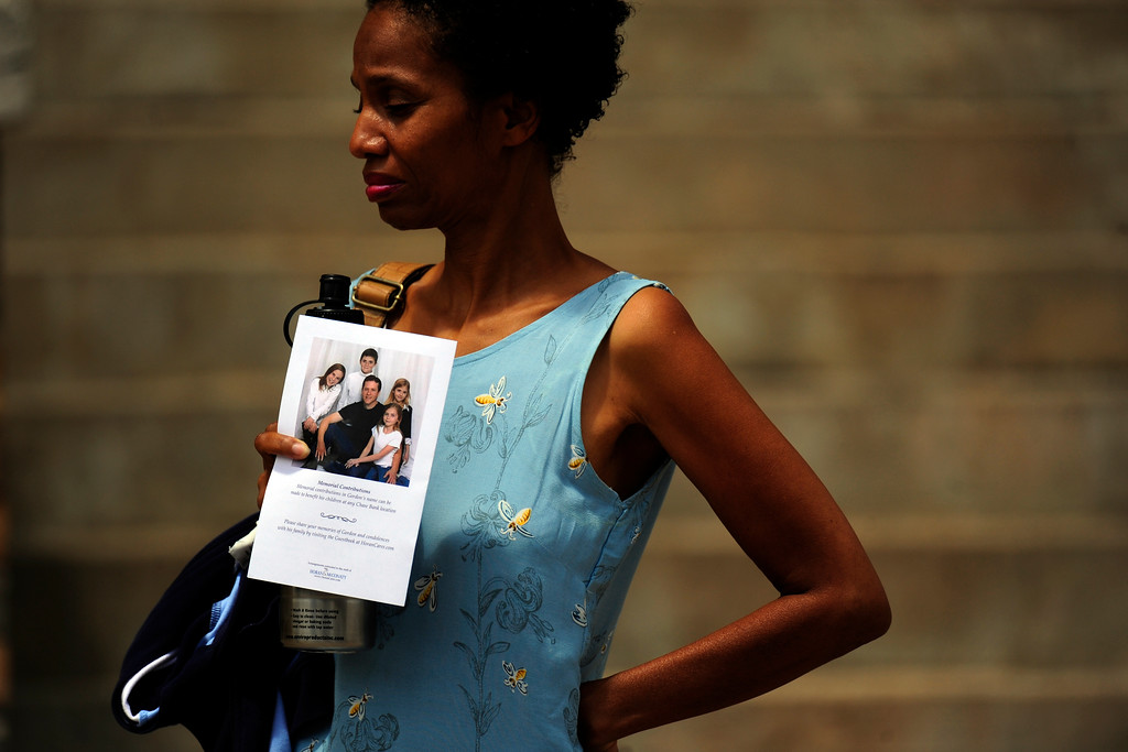 . A woman holds a program with a family picture during a memorial service, at the Pathways Church on Wednesday, July 25, 2012, for Gordon Ware Cowden, one of 12 victims who died during the Aurora Theater Shooting. AAron Ontiveroz, The Denver Post