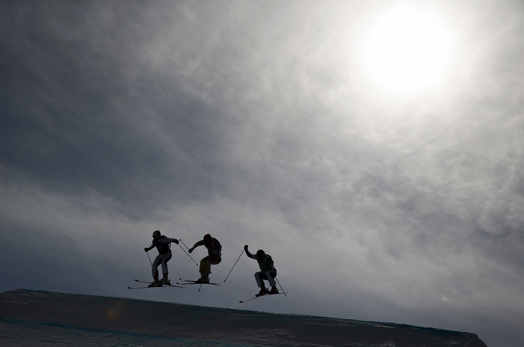 . Skiers are silhouetted against the sun during a men\'s ski cross heat at the Rosa Khutor Extreme Park, at the 2014 Winter Olympics, Thursday, Feb. 20, 2014, in Krasnaya Polyana, Russia. (AP Photo/Gero Breloer)