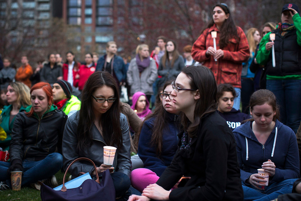 . People sit during a vigil honoring the victims of Boston Marathon bombings at the Boston Common in Boston, Massachusetts April 16, 2013. The twin blasts on Monday killed three people including an 8-year-old boy and injured 176 others, some of whom were maimed by bombs packed with ball bearings and nails. REUTERS/Shannon Stapleton
