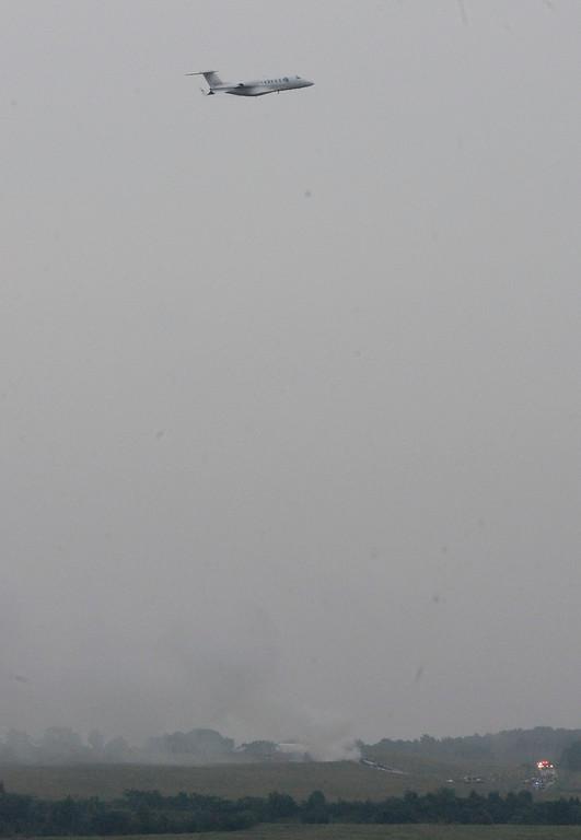 . A UPS cargo plane lies on a hill at Birmingham-Shuttlesworth International Airport after crashing on approach as a jet flies over, Wednesday, Aug. 14,  2013, in Birmingham, Ala.  (AP Photo/ AL.com, Mark Almond)