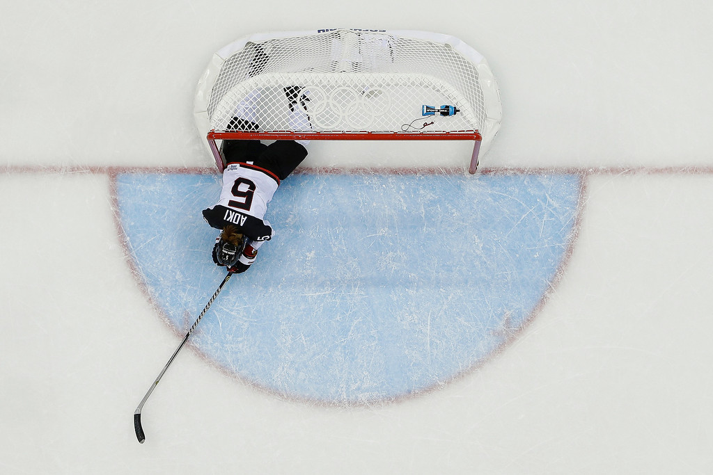 . Kanae Aoki of Japan lies on the ice after crashing into the net while trying to stop Franziska Busch\'s of Germany goal during the closing seconds of the 2014 Winter Olympics women\'s ice hockey game at Shayba Arena, Thursday, Feb. 13, 2014, in Sochi, Russia. Germany won 4-0. (AP Photo/Matt Slocum)