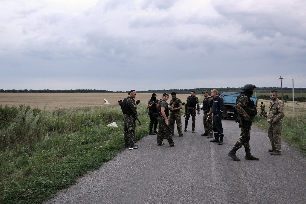 . People wearing military fatigues, stand on a road,  on July 17, 2014 at the site of the crash of a malaysian airliner carrying 295 people from Amsterdam to Kuala Lumpur, near the town of Shaktarsk, in rebel-held east Ukraine. Pro-Russian rebels fighting central Kiev authorities claimed on Thursday that the Malaysian airline that crashed in Ukraine had been shot down by a Ukrainian jet. The head of Ukraine\'s air traffic control agency said Thursday that the crew of the Malaysia Airlines jet that crashed in the separatist east had reported no problems during flight. AFP PHOTO/DOMINIQUE FAGET/AFP/Getty Images