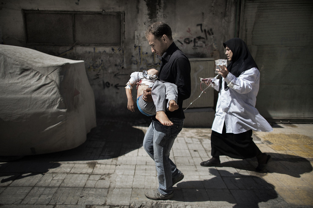 . A Syrian man carries his wounded daughter outside a hospital in the northern city of Aleppo on September 18, 2012. Syrian troops shelled several districts in Aleppo and clashed with rebels, as Damascus ally Iran proposed a simultaneous halt to the violence and a peaceful solution to the conflict. (MARCO LONGARI/AFP/GettyImages)