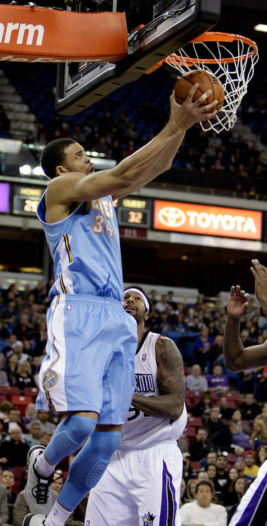 . Denver Nuggets center JaVale McGee, left, does to the basket against  Sacramento Kings forward James Johnson during the first quarter of an NBA basketball game in Sacramento, Calif., Sunday, Dec. 16, 2012.  The Nuggets won 122-97.(AP Photo/Rich Pedroncelli)