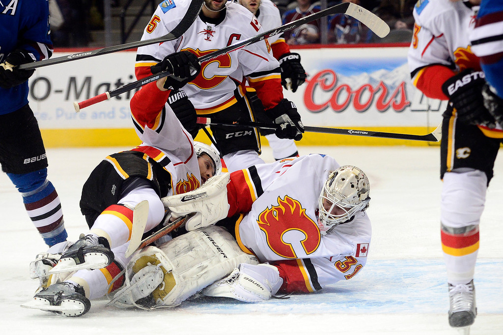 . Karri Ramo (31) of the Calgary Flames stops a shot by John Mitchell (7) of the Colorado Avalanche during the first period.  (Photo by AAron Ontiveroz/The Denver Post)