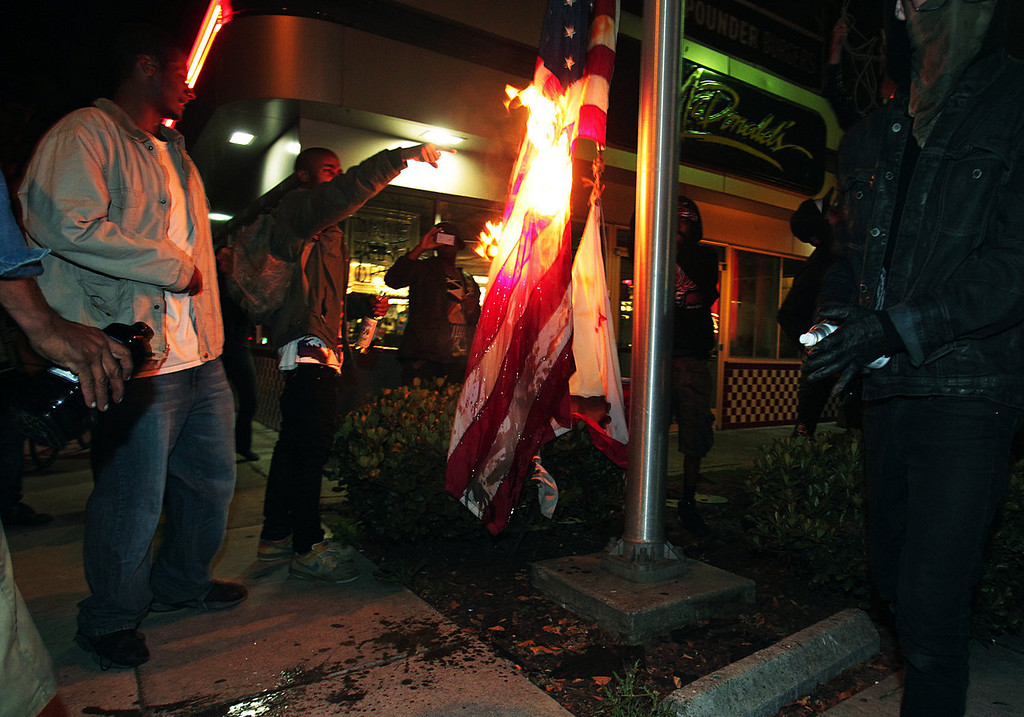 . Marchers burn a United States flag outside a fast food restaurant during a protest after George Zimmerman was found not guilty in the 2012 shooting death of teenager Trayvon Martin, early Sunday, July 14, 2013, in Oakland, Calif. Protesters angered by the acquittal Zimmerman held largely peaceful demonstrations in three California cities, but broke windows and started small street fires Oakland, police said. (AP Photo/Bay Area News Group, Anda Chu)