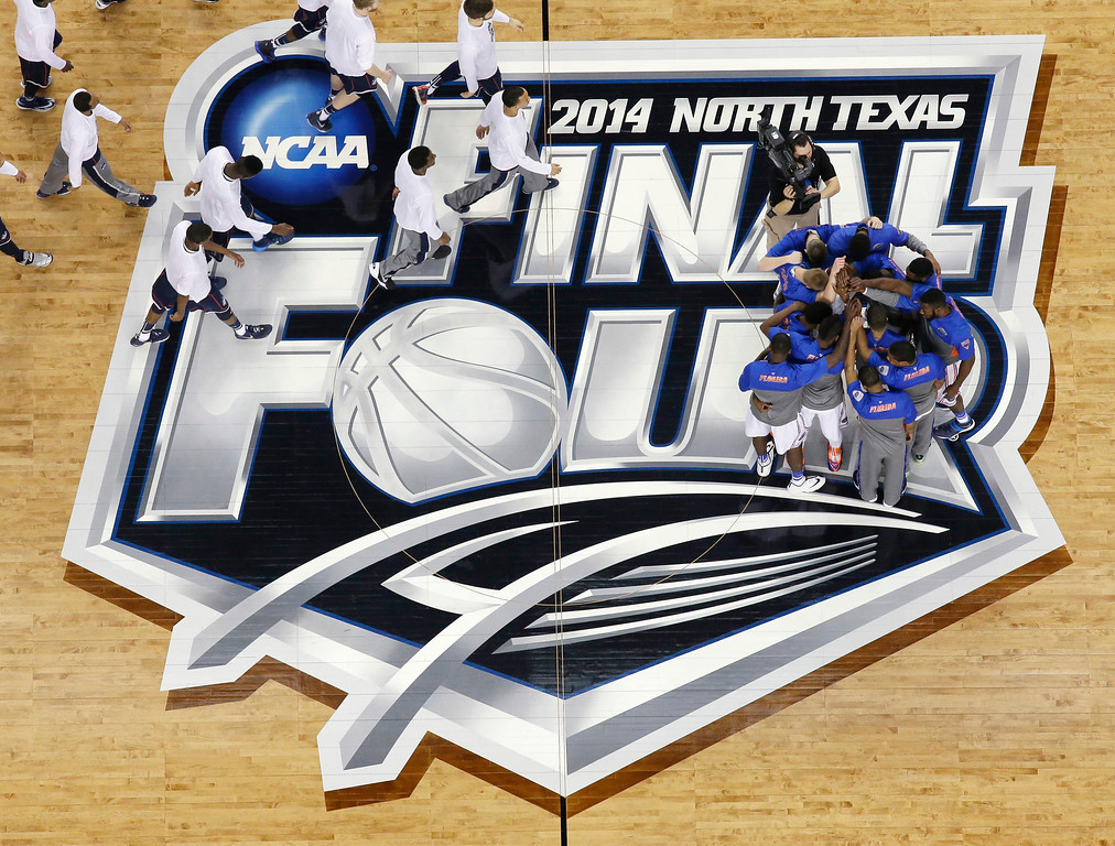 . Florida players, right, huddle at center court as Connecticut players walk past before an NCAA Final Four tournament college basketball semifinal game Saturday, April 5, 2014, in Arlington, Texas. (AP Photo/David J. Phillip)