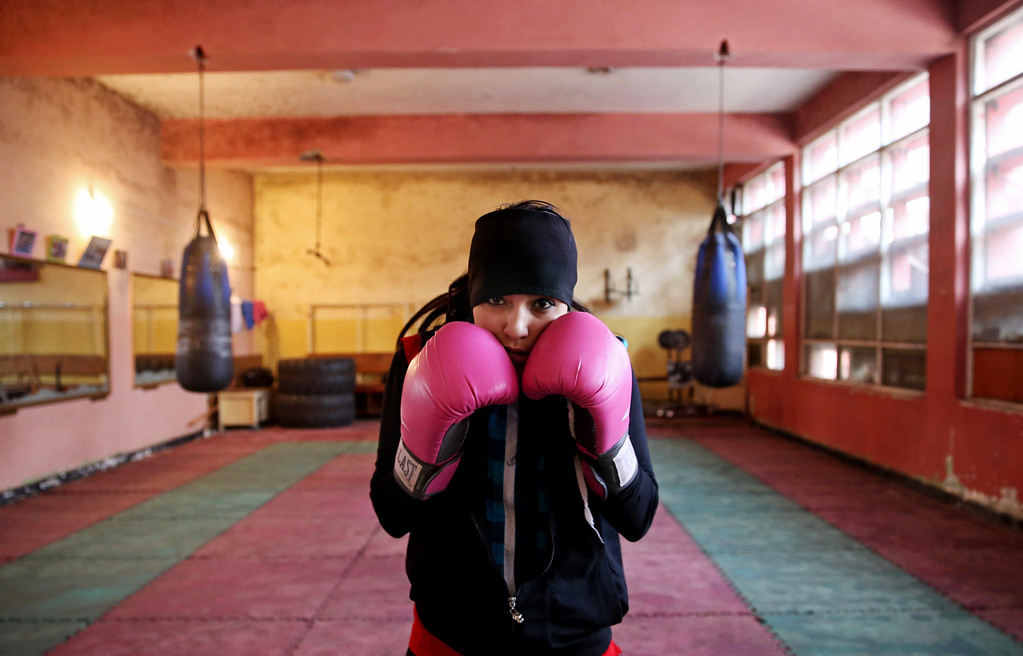 . In this Wednesday, March, 5, 2014 photo, an Afghan female boxer pauses during a practice session at the Kabul Stadium boxing club. The Afghanistan National Olympic Committee boxing club has fewer than a dozen women and little money for them. Previously nongovernmental organizations supported them. At that time there were 25 young women who received a salary the equivalent of $100 per month and transportation to and from the Kabul Stadium where they train. (AP Photo/Massoud Hossaini)