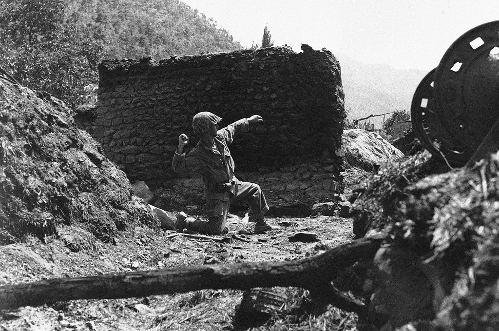 . A US 25th Div. Inf. gets set to heave a grenade at enemy sniper hidden in a village 20 miles north Taegu on Naktong River front in Korea on August 29, 1950. (AP Photo)