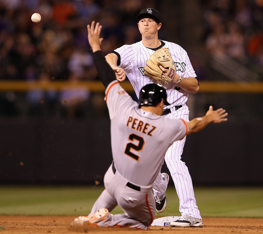 . Second baseman DJ LeMahieu #9 of the Colorado Rockies turns a doubel play on Juan Perez #2 of the San Francisco Giants ona ground ball by Pablo Sandoval #48 of the San Francisco Giants to end the eighth inning at Coors Field on April 22, 2014 in Denver, Colorado.  (Photo by Doug Pensinger/Getty Images)