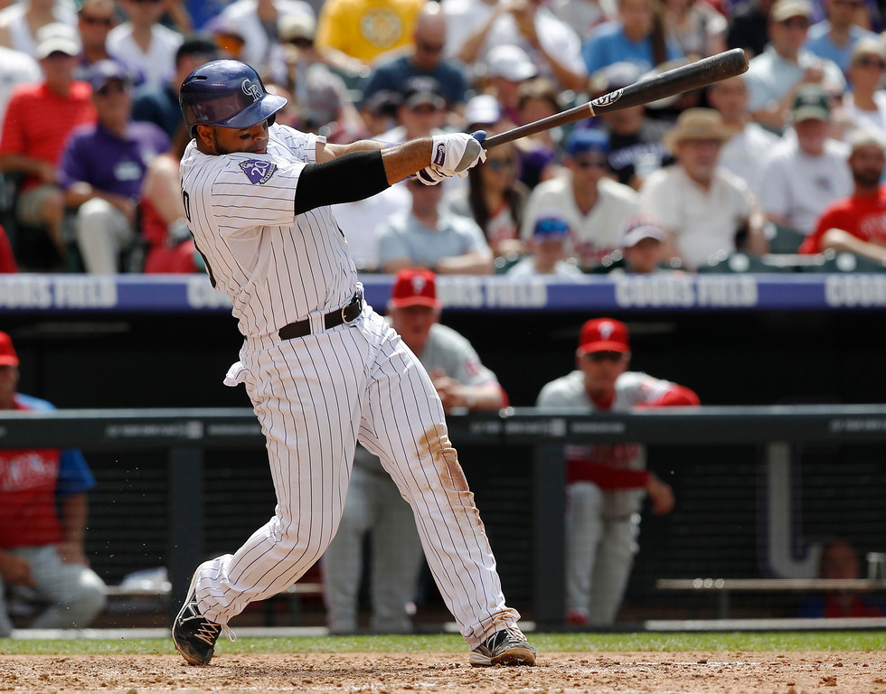 . Colorado Rockies\' Wilin Rosario follows through with his swing after connecting for an RBI-double against the Philadelphia Phillies in the fourth inning of a baseball game in Denver, Saturday, June 15, 2013. (AP Photo/David Zalubowski)