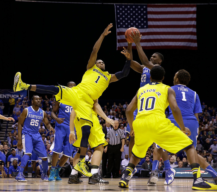 . Michigan\'s Glenn Robinson III (1) and Kentucky\'s Alex Poythress (22) go after a rebound during the second half of an NCAA Midwest Regional final college basketball tournament game Sunday, March 30, 2014, in Indianapolis. (AP Photo/David J. Phillip)