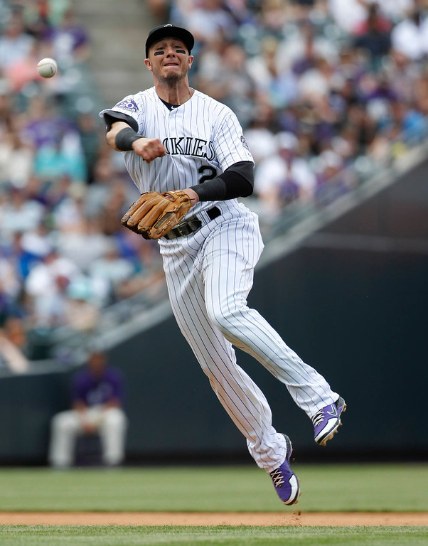 . Colorado Rockies shortstop Troy Tulowitzki jumps in the air as he throws to put out San Francisco Giants\' Brandon Crawford in the fourth inning of a baseball game in Denver on Sunday, May 19, 2013. (AP Photo/David Zalubowski)