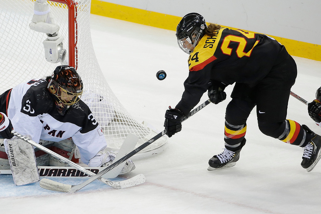 . Goalkeeper Nana Fujimoto of Japan blocks Lisa Christine Schuster\'s of Germany shot at the goal during the 2014 Winter Olympics women\'s ice hockey game at Shayba Arena, Thursday, Feb. 13, 2014, in Sochi, Russia. (AP Photo/Matt Slocum)