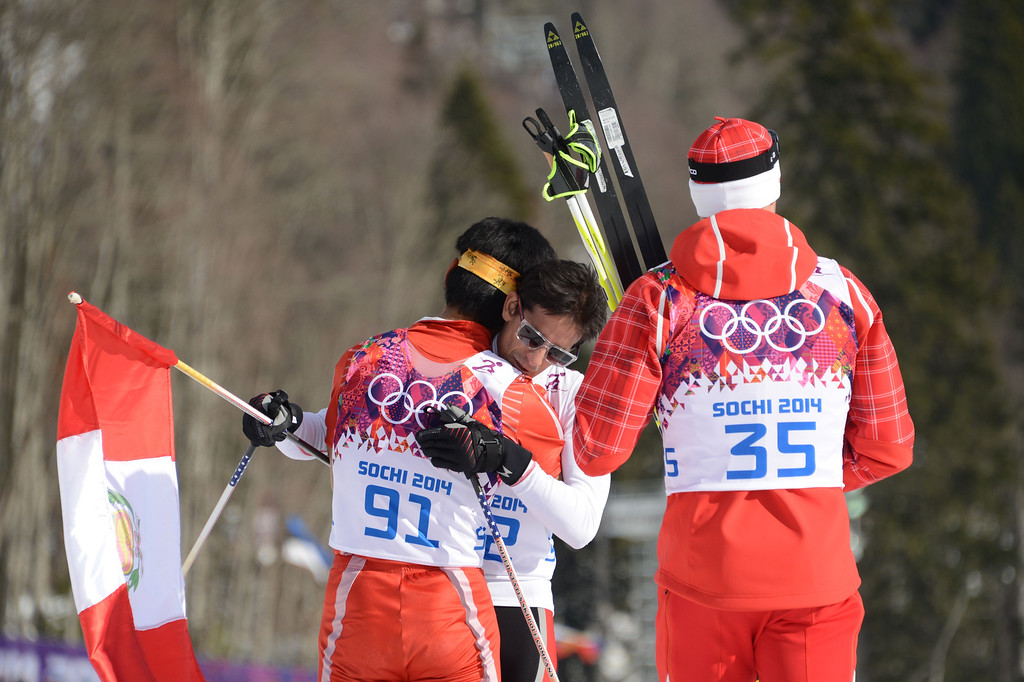 . Peru\'s Roberto Carcelen (C) is congratulated by Nepal\'s Dachhiri Sherpa (L) and gold winner Switzerland\'s Dario Cologna (R) after crossing the finish line  in the Men\'s Cross-Country Skiing 15km Classic at the Laura Cross-Country Ski and Biathlon Center during the Sochi Winter Olympics on February 14, 2014.  AFP PHOTO / KIRILL KUDRYAVTSEV/AFP/Getty Images
