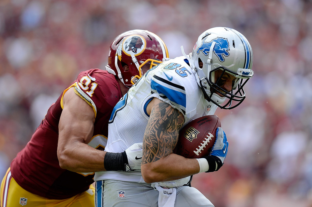 . LANDOVER, MD - SEPTEMBER 22:  Tony Scheffler #85 of the Detroit Lions is tackeld by Ryan Kerrigan #91 of the Washington Redskins after catching a pass in the second quarter during a game at FedExField on September 22, 2013 in Landover, Maryland.  (Photo by Patrick McDermott/Getty Images)