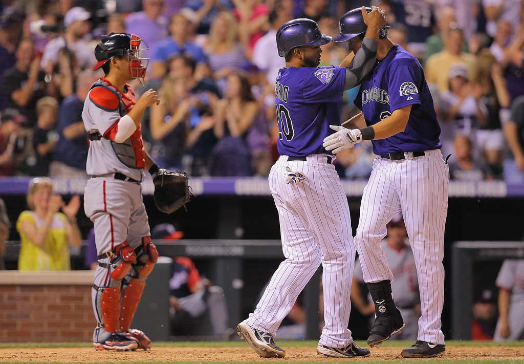 . Tyler Colvin #21 of the Colorado Rockies is welcomed home by Wilin Rosario #20 of the Colorado Rockies after his two run home run off of Drew Storen #22 of the Washington Nationals as catcher Kurt Suzuki #24 of the Washington Nationals looks on in the eighth inning at Coors Field on June 11, 2013 in Denver, Colorado. Colvin had two two run home runs in the game as the Rockies defeated the Nationals 8-3.  (Photo by Doug Pensinger/Getty Images)