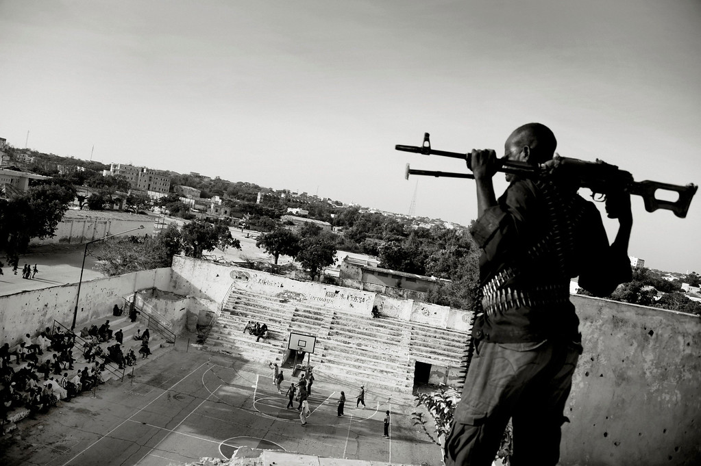". Jan Grarup of Denmark, a photographer working for Laif Agency, has won the first prize in the Sports Features Stories category of the World Press Photo Contest 2013 with the series ""Women\'s Basketball, Mogadishu, Somalia\"". The picture shows an armed guard, paid by the Somali basketball association, watching over and protecting a women\'s basketball team as they play in Mogadishu, taken on February 21, 2012 and distributed by the World Press Photo Foundation February 15, 2013.  REUTERS/Jan Grarup/Laif/World Press Photo/Handout"