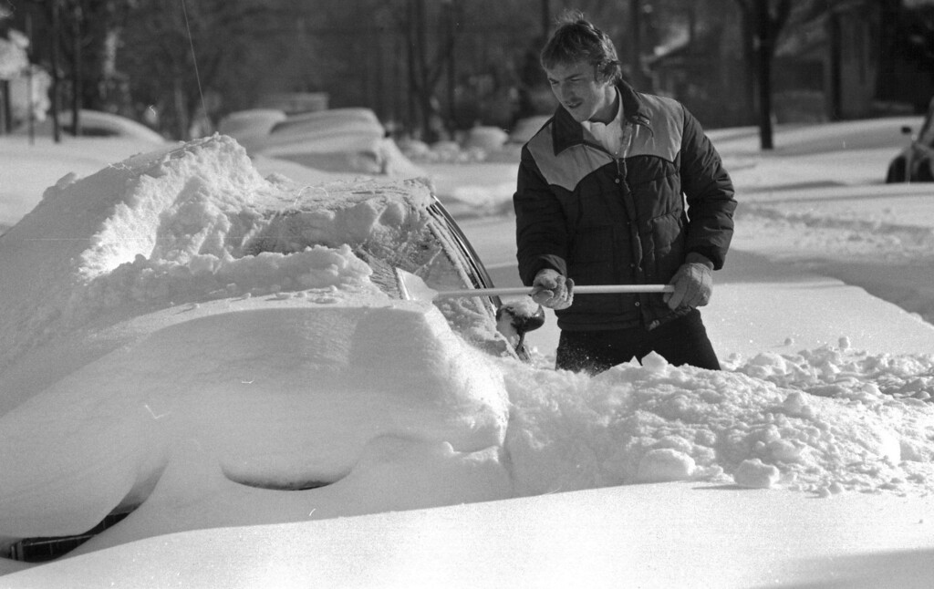 . A man uses a broom to clear off his car after the Blizzard of \'82. Denver Post Library Archive