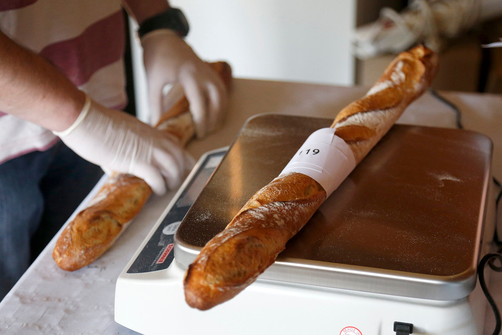 . An assistant weighs baguettes registered in the competition for the \'Grand Prix de la Baguette de la Ville de Paris\' (Best Baguette of Paris 2013) annual prize at the Chambre Professionnelle des Artisans Boulangers Patissiers in Paris April 25, 2013. The baguette is a French cultural symbol par excellence and the competition saw 203 Parisian bakers who compete for recognition as finest purveyor of one of France\'s most iconic staples. The baguettes are registered, given anonymous white wrappings and an identification number. They are then carefully weighed and measured to ensure they do not violate the contest\'s strict rules. 52 entries were withdrawn for failing to measure between 55-70cm long or not matching the acceptable weight of between 250-300g. Every year, the winner earns the privilege of baking bread for the French President.   REUTERS/Charles Platiau